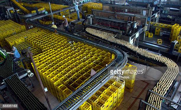 Employees work at the beer production line in Guangzhou Zhujiang Beer Group Company factory on August 6 2005 in Guangzhou of Guangdong Province South...