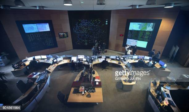 Employees work at the dispatching room of the national operating center of French electricity transport network operator RTE on February 26, 2018 in...