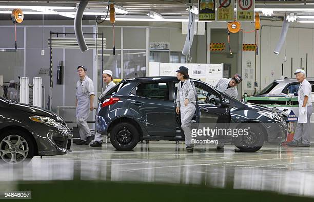 Employees Work At The End Of Embly Line Inside Mazda Motor Corp S Ujina Plant In