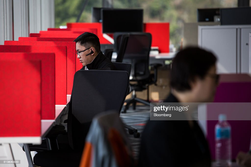 Employees work at the Microsoft Corp. Office and Experience Center during a media event for the opening of the workspace in Hong Kong, China, on Friday, March 4, 2016. Microsoft is rolling out a new service for its Windows 10 operating system to help large businesses detect hackers, security threats and unusual behavior on their networks, rivaling companies like FireEye Inc. and Symantec Corp. Photographer: Billy H.C. Kwok/Bloomberg via Getty Images