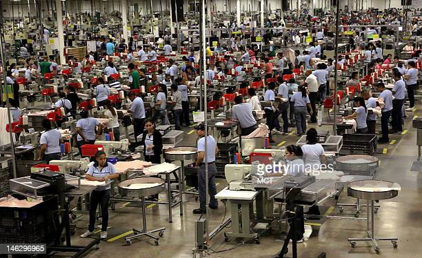 Employees work at the production line at a factory in Ciudad Acuna Coahuila state Mexico May 18 2012 Mexico's economic model of free trade and low...