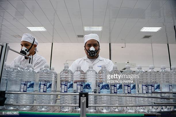Employees work at the production line of bottled mineral water at Fort Tiuna the main complex of the Armed Forces of Venezuela in Caracas on March 10...