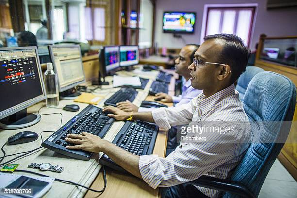 Employees work at their desks in a brokerage firm in Mumbai India on Tuesday June 7 2016 Indian central bank Governor Raghuram Rajan kept the...