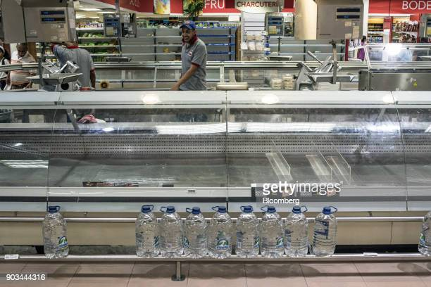Employees work behind empty counters in the deli section of a grocery store in Caracas Venezuela on Tuesday Jan 9 2018 Hordes of desperate shoppers...