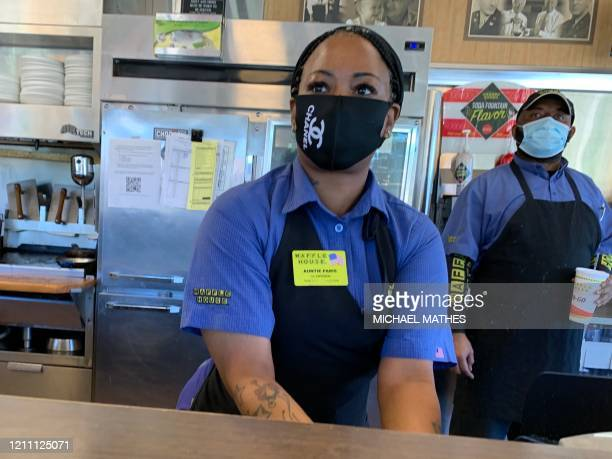 Employees work behind the counter of a Waffle House for in Atlanta as the state of Georgia relaxed its Coronavirus pandemic restrictions to allow...