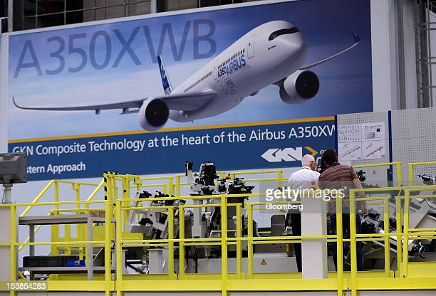 Employees work beneath a giant poster of an Airbus SAS A350 XWB aircraft produced by European Aeronautic Defence Space Co inside GKN Plc's Aerospace...
