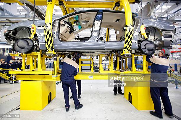 Employees work beneath a Maserati Quattroporte luxury automobile as it travels along the production line at Fiat SpA's Grugliasco factory in Turin...