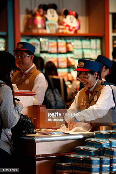 Employees work in a shop which has its lights darkened to save electricity at Tokyo Disneyland operated by Oriental Land Co in Urayasu city Chiba...