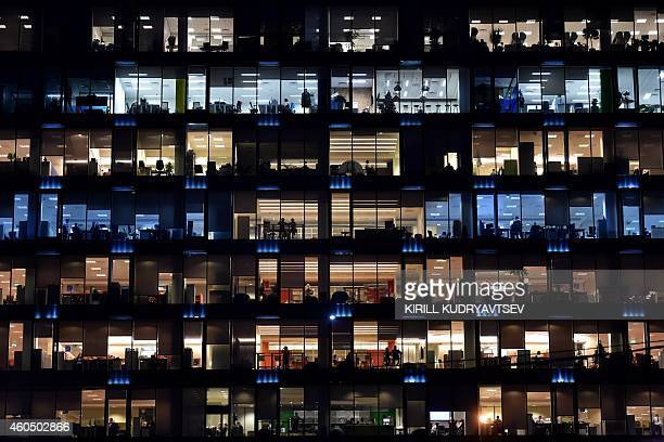 Employees work in an office in Moscow on December 15 2014 The Russian ruble tumbled 95 percent Monday to new record lows as falling crude prices...