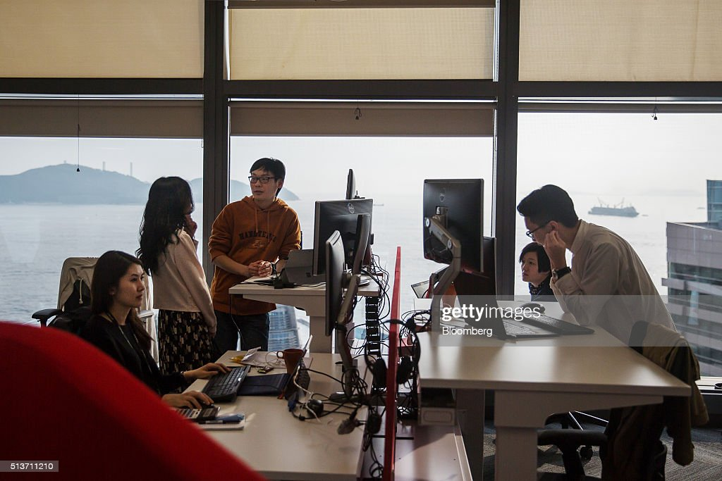 Employees work in front of computers at the Microsoft Corp. Office and Experience Center during a media event for the opening of the workspace in Hong Kong, China, on Friday, March 4, 2016. Microsoft is rolling out a new service for its Windows 10 operating system to help large businesses detect hackers, security threats and unusual behavior on their networks, rivaling companies like FireEye Inc. and Symantec Corp. Photographer: Billy H.C. Kwok/Bloomberg via Getty Images