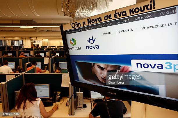 Employees work in the customer support and call center beneath a screen showing Nova TV at Forthnet SA Greece's largest payTV provider in Athens...
