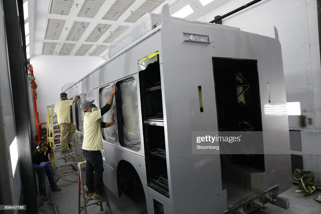 Employees work in the paint booth on an electric bus at the BYD Coach and Bus factory in Lancaster, California, U.S., on Thursday, Oct. 5, 2017. BYD unveiled the newly expanded 450,000 square foot factory on Friday, North America's largest electric bus manufacturing facility. Photographer: Patrick T. Fallon/Bloomberg via Getty Images