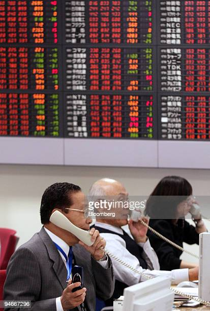 Employees work in the trading room at a securities company in Tokyo Japan on Monday Nov 19 2007 Japan's Topix index slipped reversing earlier gains...