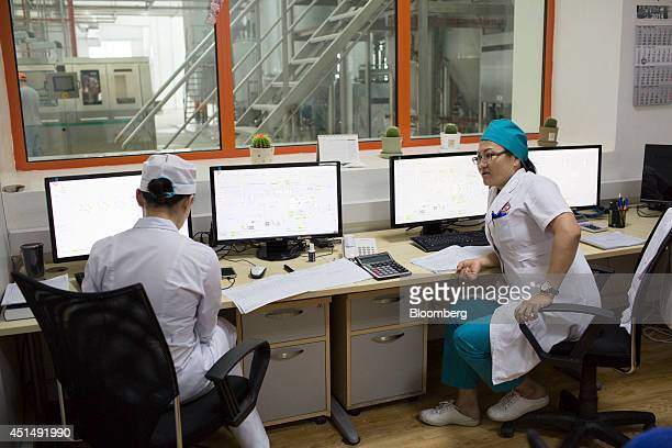 Employees work inside a control room at the APU JSC dairy plant in Ulaanbaatar Mongolia on Tuesday June 24 2014 APU is Mongolia's largest spirit and...