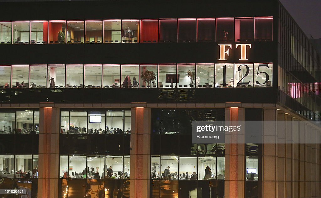 Employees work inside the Financial Times newspaper headquarters which are bathed in pink light to mimic the color of the publication's paper, as part of their 125th anniversary celebrations, in London, U.K. on Wednesday, Feb. 13, 2013. Pearson Plc, owner of the Financial Times newspaper, cut its forecast for 2012 and predicted a difficult 2013, as tougher market conditions hit earnings at its professional education and FT Group units. Photographer: Chris Ratcliffe/Bloomberg via Getty Images