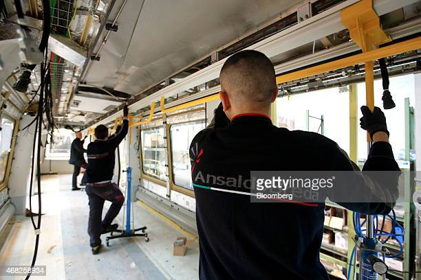 Employees work inside the shell of a Copenhagen metro train carriage during manufacture at AnsaldoBreda SpA's rail car plant in Naples Italy on...
