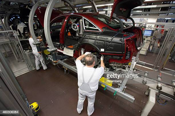 Employees work inside the wheel arches of an Audi A6 automobile as it passes along the production line inside the Audi AG factory in Neckarsulm...