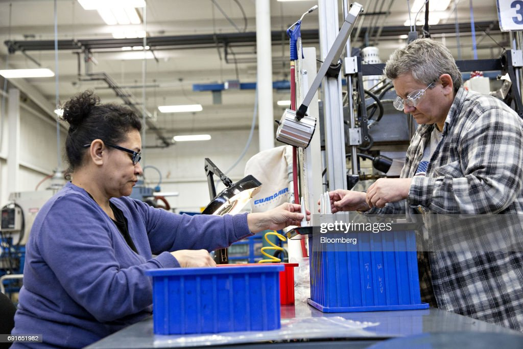 Employees work near a plastic injection molding machine at the