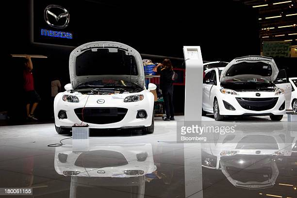 Employees work near Mazda automobiles produced by Mazda Motor Corp as they stand on the company's floor display at the 65th Frankfurt International...