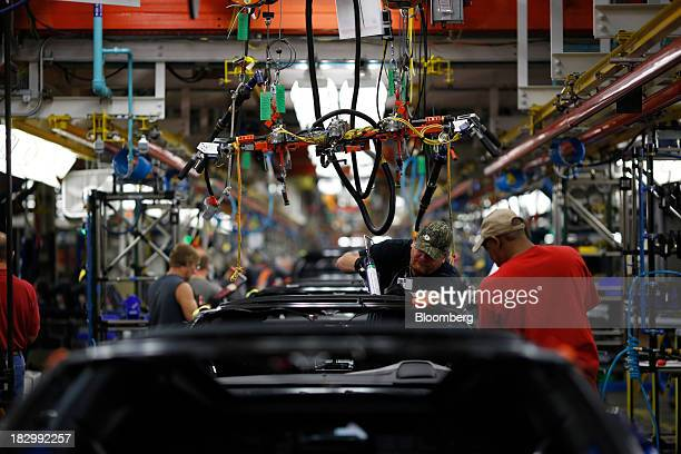 Employees work on 2014 Chevrolet Corvette Stingrays at the General Motors Co. Bowling Green Assembly Plant in Bowling Green, Kentucky, U.S., on...