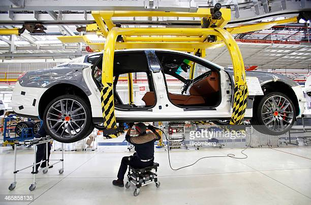Employees work on a Maserati Ghibli luxury automobile produced by Maserati SpA as it travels along the production line at Fiat SpA's Grugliasco...
