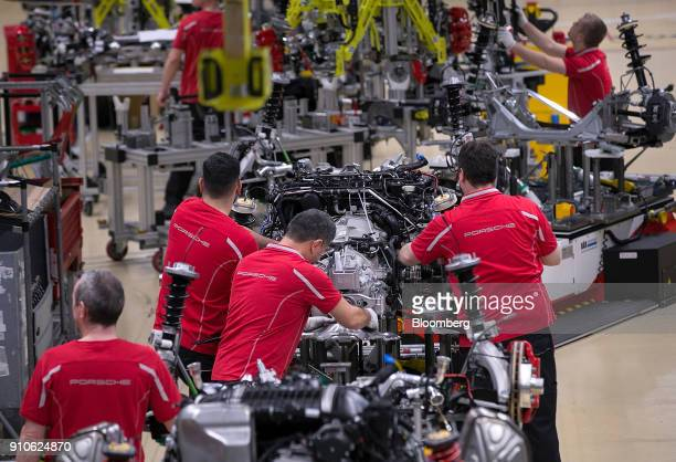 Employees work on a powertrain system on the production line inside the Porsche AG luxury automobile factory in Stuttgart Germany on Friday Jan 26...