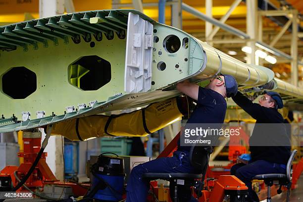 Employees work on a section of Airbus A320 wing inside the A320/A330 wing assembly building at the Airbus Group NV assembly plant in Broughton UK on...