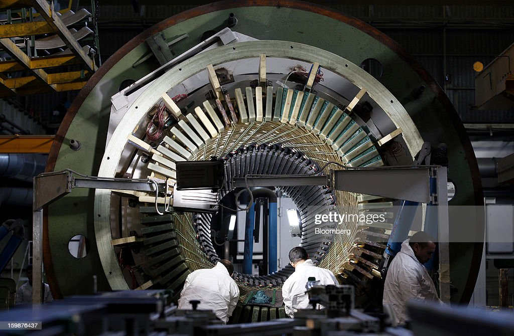 Employees work on a section of turbogenerator during assembly at Ansaldo Energia SpA's power-plant production facility in Genoa, Italy, on Friday, Jan. 18, 2013. Finmeccanica SpA is seeking binding bids for assets, including a majority stake in Ansaldo Energia, by Jan. 23, while a final decision will be made at a later board meeting, Ansa reported Jan. 16. Photographer: Alessia Pierdomenico/Bloomberg via Getty Images