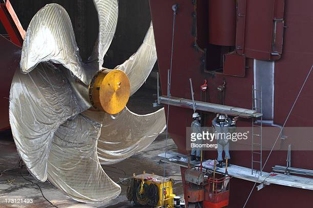 Employees work on a ship under construction near a propeller part at the Hyundai Heavy Industries Co shipyard in Ulsan South Korea on Wednesday July...