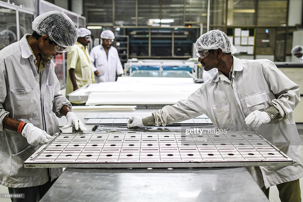 Employees work on a solar panel placed in an assembly jig on the solar photovoltaic module production line at the Tata Power Solar Systems Ltd. manufacturing plant in Bangalore, India, on Tuesday, June 11, 2013. Tata Groups solar unit is expanding its business building plants for customers, forecasting that offices and factories will be paying more for grid power than solar by 2016 in most Indian states. Photographer: Dhiraj Singh/Bloomberg via Getty Images