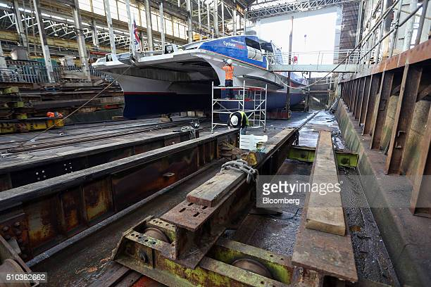 Employees work on a Thames Clipper catamaran at Turks boatyard in Chatham UK on Thursday Oct 29 2015 The Thames Clipper river bus service added two...