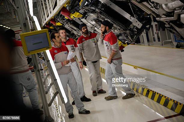 Employees work on Alfa Romeo Giulia automobiles on the production line at Fiat Chrysler Automobiles NV's Alfa Romeo assembly plant in Cassino Italy...