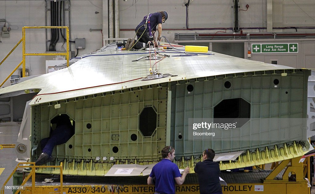 Employees work on an Airbus A330 passenger aircraft wing during production at the company's factory in Broughton, U.K., on Monday, Feb. 4, 2013. Airbus SAS won a $9 billion order from Steven Udvar-Hazy's Air Lease Corp. that includes 25 A350 wide-body jets, a competitor to Boeing Co.'s grounded 787 Dreamliner. Photographer: Paul Thomas/Bloomberg via Getty Images
