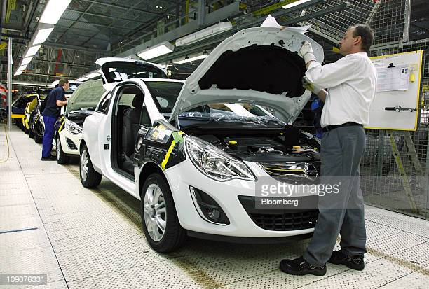 Employees work on an Opel Corsa automobile as it passes along the production line at the General Motor Co's Adam Opel plant in Eisenach Germany on...