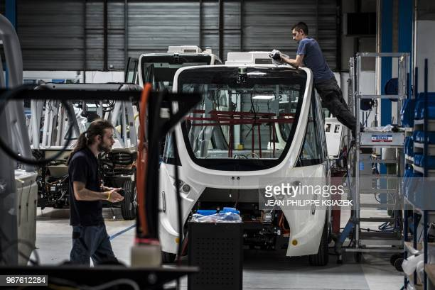 Employees work on April 23 2018 on an autonomous driverless and electric bus shuttle at the NAVYA plant in Bron near Lyon central eastern France The...