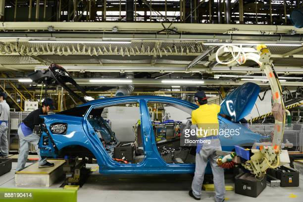 Employees work on automobile assembly on the Prius hybrid plug-in vehicle production line inside the Toyota Motor Corp. Tsutsumi plant in Toyota...