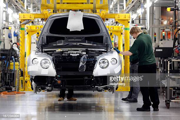 Employees work on Bentley Continental automobiles as they travel along the production line inside the Bentley Motors Ltd workshop in Crewe UK on...