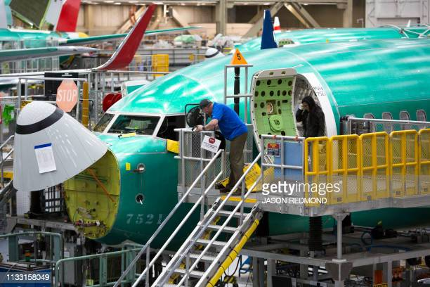 Employees work on Boeing 737 MAX airplanes at the Boeing Renton Factory in Renton Washington on March 27 2019 Embattled aviation giant Boeing will do...