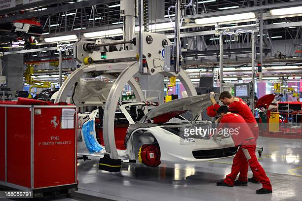 Employees work on Ferrari tourism cars held on pincers on the assembly line of the Ferrari factory on December 5 2012 in Maranello The Ferrari 45...