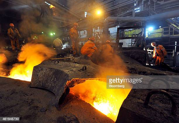Employees work on maintenance while molten iron runs through floor channels after leaving the blast furnace at the Zelezara Smederevo doo steel plant...