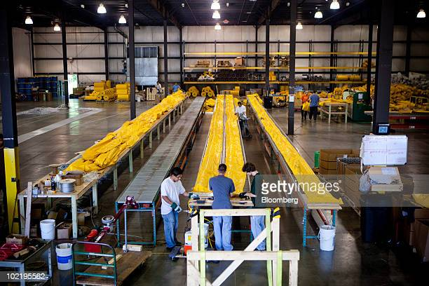Employees work on oil booms in the last stages of production at Prestige Products in Walker Michigan US on Thursday June 17 2010 Michigan's depressed...
