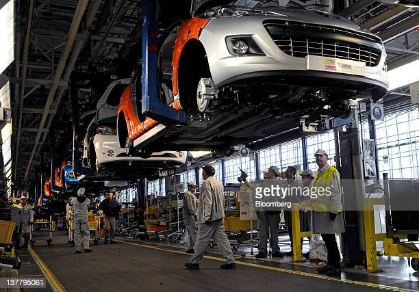 Employees work on PSA Peugeot Citroen automobiles as they travel along the assembly line at the company's Poissy production facility in Paris France...