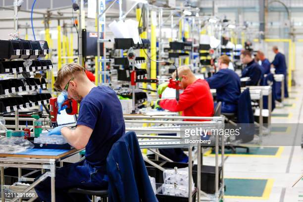 Employees work on the absorber component of a ventilator on the production line in an adapted hangar at the Airbus SE assembly plant in Broughton,...