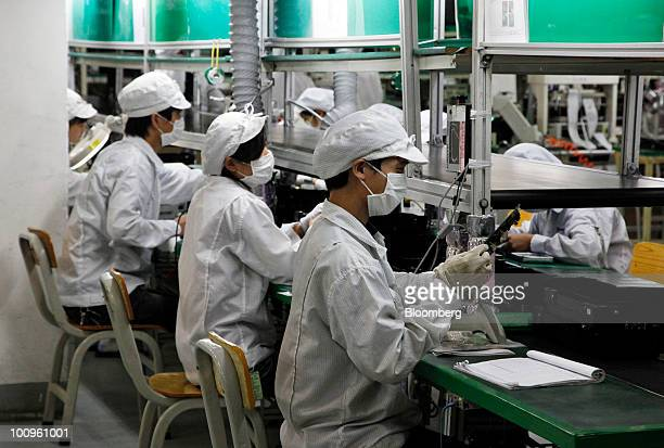 Employees work on the assembly line at Hon Hai Group's Foxconn plant in Shenzhen Guangdong province China on Wednesday May 26 2010 Gou said nine of...