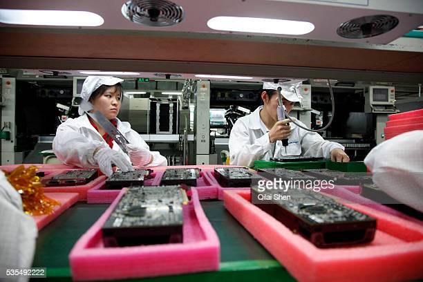 Employees work on the assembly line at Hon Hai Group's Foxconn plant in Shenzhen China on Wednesday May 26 2010 Hon Hai is the parts supplier for...