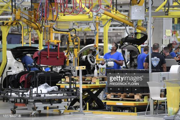 Employees work on the assembly line at the Smart car factory in Hambach, eastern France, on July 30 before a meting of French Junior Industry...