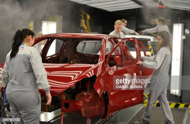 Employees work on the assembly line of the Peugeot 208 car by French car maker PSA Peugeot Citroen at the company's automobile factory in Trnava...