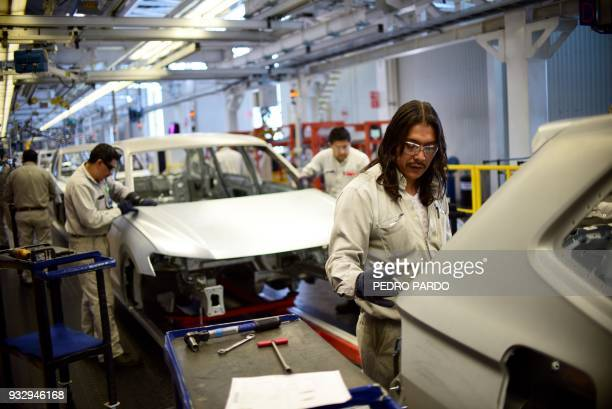 Employees work on the assembly line of the Tiguan model at the Volkswagen car plant in Puebla central Mexico on March 16 2018 / AFP PHOTO / Pedro...