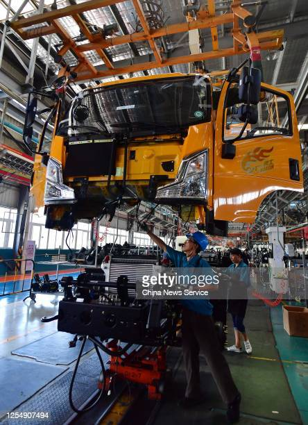 Employees work on the assembly line of trucks at a factory of China National Heavy Duty Truck Group Co., Ltd on July 7, 2020 in Sanming, Fujian...