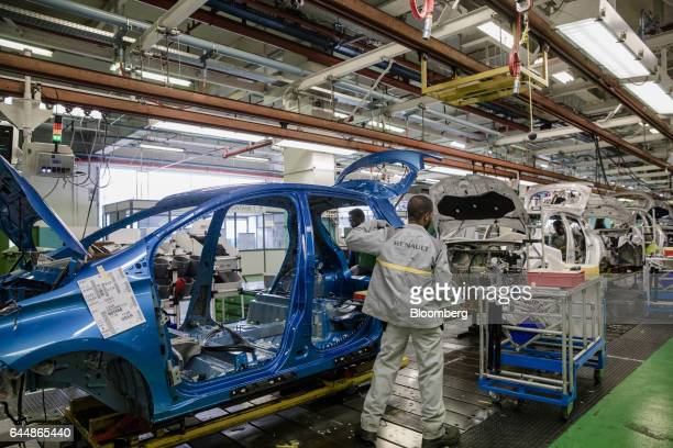Employees work on the body shell of a Renault Zoe automobile left as a Renault Clio sits behind on the assembly line inside the Renault SA factory in...